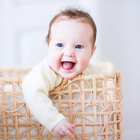 Photo pour Adorable laughing baby sitting in a laundry basket - image libre de droit