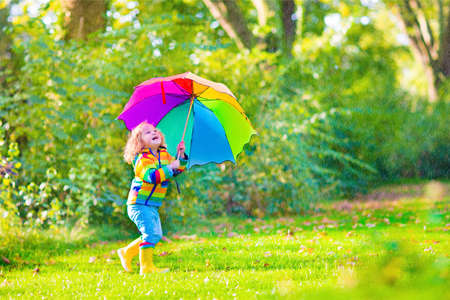 Funny cute curly toddler girl wearing yellow waterproof coat and boots holding colorful umbrella playing in the garden by rain and sun weather on a warm autumn or summer dayの写真素材