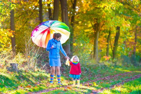 Happy young mother and her adorable toddler daughter, cute curly little girl in a colorful dress and warm coat, playing together in a beautiful autumn park enjoying a sunny fall day outdoorsの写真素材
