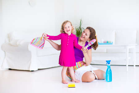 Photo pour Young happy mother and her little daughter, cute toddler girl, cleaning the house together sweeping the floor in a white sunny living room with modern interion and big white couch - image libre de droit