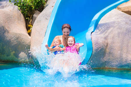 Young happy mother and two children, baby boy and toddler girl having fun at water sllide in a tropical pool on a hot summer day