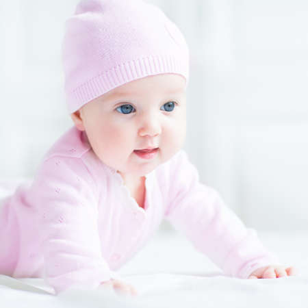 Photo pour Happy smiling baby girl in a pink knitted hat - image libre de droit