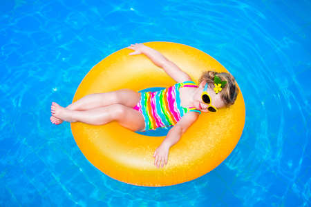 Foto de Cute funny little toddler girl in a colorful swimming suit and sun glasses relaxing on an inflatable toy ring floating in a pool having fun during summer vacation in a tropical resort - Imagen libre de derechos
