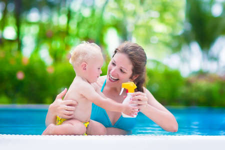 Young mother and cute baby boy enjoying summer vacation in a tropical resort at a swimming pool, parent applying sun screen using lotion spray for safe tan and skin care