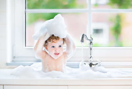 Funny little baby girl with wet curly hair taking a bath in a kitchen sink with lots of foam playing with water drops and splashes next to a big window with garden view