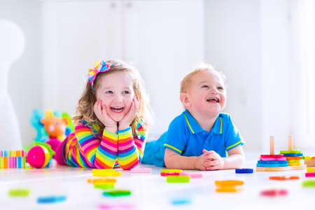 Kids playing with wooden toys. Two children, cute toddler girl and funny baby boy, playing with wooden toy blocks, building towers at home or day care. Educational child toys for preschool and kindergarten.