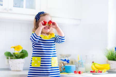 Little girl preparing breakfast in white kitchen. Healthy food for children. Child drinking milk and eating fruit. Happy smiling preschooler kid enjoying morning meal, cereal, banana and strawberry.