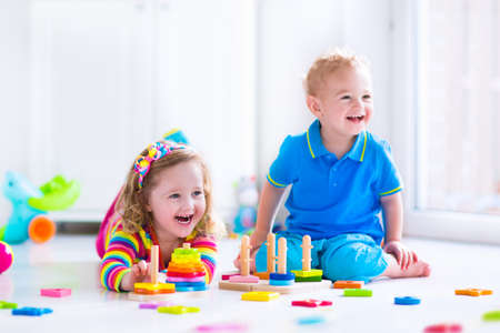 Kids playing with wooden toys. Two children, cute toddler girl and funny baby boy, playing with toy blocks, building towers at home or day care. Educational child toys for preschool and kindergarten.