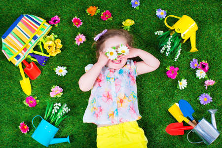 Photo pour Kids gardening. Children with garden tools. Child with watering can and shovel. Little kid watering flowers. Girl relaxing on green backyard lawn in summer. - image libre de droit
