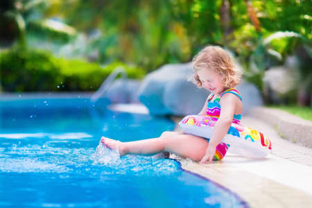 Photo pour Kids in swimming pool. Children swim outdoors. Toddler child during vacation in a tropical resort with palm trees. Little girl playing on a beach. Active kid in summer with colorful toy floating ring. - image libre de droit