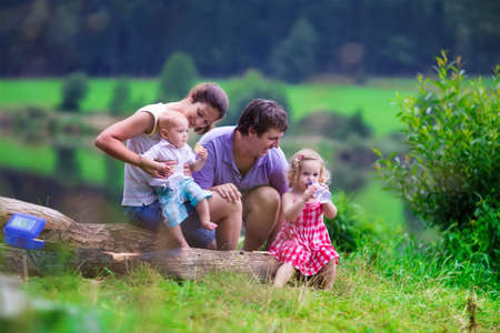 Foto de Family on summer hike. Young parents with kids hiking next to a lake. Mother, father and two children having picnic outdoors. Active trekking with baby and toddler. Beautiful nature of Germany. - Imagen libre de derechos