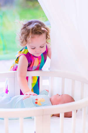 Kids in bed. Two children playing together in a white sunny bedroom. Little girl meets her newborn baby brother. Siblings play indoors. Infant boy in a white bassinet with his sister. Kid in a crib.