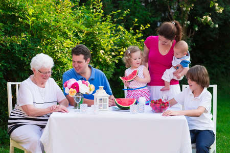Big family with children have lunch outdoors. Parents with 3 kids and grandmother eat in the garden. Picnic for mother father baby boy toddler girl and teenager child. Generations and retirement.