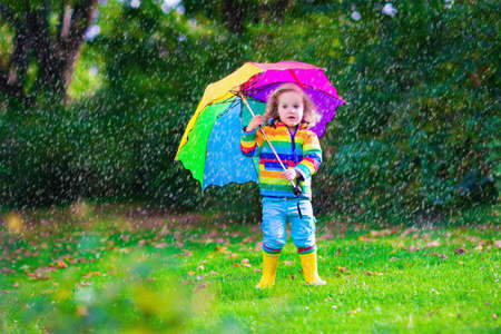 Child with colorful umbrella playing in the rain. Kids play outdoors by rainy weather. Toddler kid in coat and waterproof boots jumping in autumn garden. Fall fun for children raining in the park.の写真素材