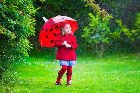 Little girl with red umbrella playing in the rain. Kids play outdoors by rainy weather in fall. Autumn outdoor fun for children. Toddler kid in raincoat and boots walking in the garden. Summer shower.の写真素材