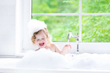 Child taking bath. Little baby in a bath tub washing hair with shampoo and soap. Kids playing with foam and water splashes. White bathroom with window. Clean kid after shower. Children hygiene.