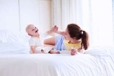 Mother and baby relaxing in white bedroom