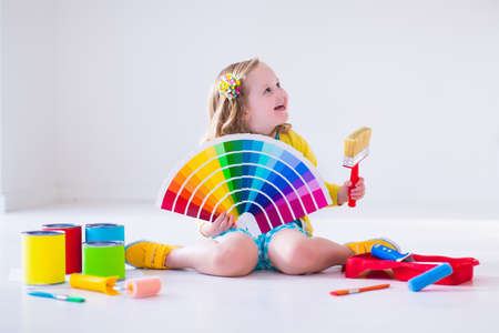 Photo pour Family remodeling house. Home remodel and renovation. Kids painting walls with colorful brush and roller. Children paint wall. Choice of bright color on sample palette for child nursery or kid room. - image libre de droit