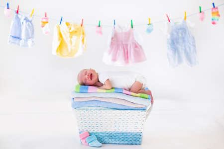 Newborn baby on a pile of clean dry towels. New born child after bath in a towel. Family washing clothes. Kids wear hanging on a line. Infant apparel, textile for children. Smiling boy after shower.