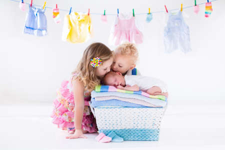 Photo pour Newborn child on a pile of clean dry towels. Brother and sister kissing little sibling. Siblings bonding. Twin toddler kids kiss baby boy. New born kid after bath in a towel. Family washing clothes. - image libre de droit