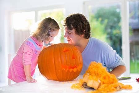 Foto de Family carving pumpkin at Halloween. Parents and children decorate the house. Kids and parents trick or treat. Father and child carve squash at home. Toddler kid with jack-o-lantern. - Imagen libre de derechos