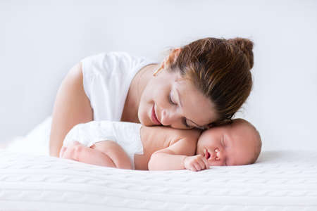Young mother hugging her newborn child. Mom nursing baby. Woman and new born boy relax in a white bedroom. Family at home. Love, trust and tenderness concept. Bedding and textile for nursery.
