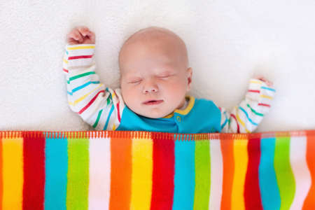 Photo pour Newborn baby boy in bed. New born child sleeping under a colorful blanket. Children sleep. Bedding for kids. Infant napping in bed. Healthy little kid shortly after birth. Clothing for kids. - image libre de droit