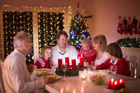 Big family with three children celebrating Christmas at home. Festive dinner at fireplace and Xmas tree. Parent and kids eating at fire place in decorated room. Child lighting advent wreath candle.の写真素材