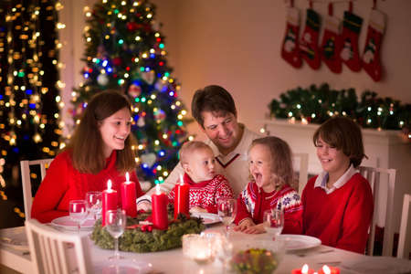 Photo pour Big family with three children celebrating Christmas at home. Festive dinner at fireplace and Xmas tree. Parent and kids eating at fire place in decorated room. Child lighting advent wreath candle. - image libre de droit