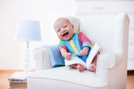 Cute funny baby boy reading a book sitting in a white chair at home. Children read books in a library seat. Nursery and playroom interior for kids. Early development and learning for young kid.
