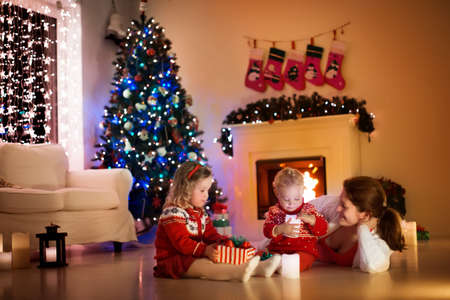 Parents and kids relax at fireplace on Christmas eve. Family with children celebrating Xmas. Decorated living room with tree, fire place and candles. Winter evening at home. Boy and girl open presentsの写真素材