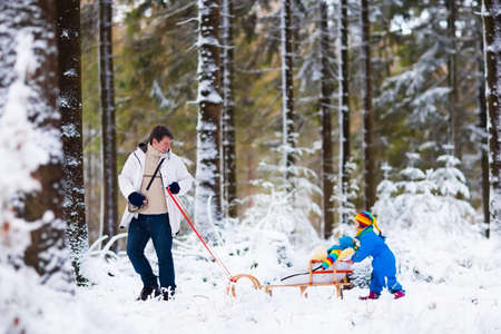 Father and kids enjoy a sleigh ride in winter forest. Baby boy and toddler girl sled in snowy park. Dad pulling children on sledge. Parent and child sledding. Family outdoor fun on Christmas vacationの写真素材