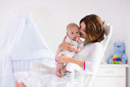Photo pour Young mother holding her newborn child. Mom nursing baby. Woman and new born boy in white bedroom with rocking chair and blue crib. Nursery interior. Mother playing with laughing kid. Family at home - image libre de droit