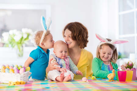 Photo pour Mother and children painting colorful eggs. Mom, toddler, preschooler and baby with bunny ears paint and decorate Easter egg. Parent and kids play indoors in spring. Family celebrating Easter at home. - image libre de droit
