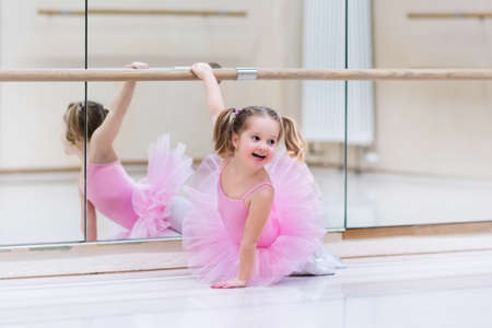 Photo pour Little ballerina girl in a pink tutu. Adorable child dancing classical ballet in a white studio. Children dance. Kids performing. Young gifted dancer in a class. Preschool kid taking art lessons. - image libre de droit