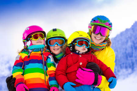 Photo for Mother and children skiing in the mountains. Active mom and three kids with safety helmet, goggles and poles. Ski lesson for young children. Winter sport and snow fun for family. Child learning to ski - Royalty Free Image
