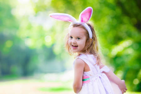 Photo for Little girl having fun on Easter egg hunt. Kids in bunny ears and rabbit costume. Children searching for eggs in the garden. Toddler kid playing outdoor. Child laughing and smiling on a spring day - Royalty Free Image