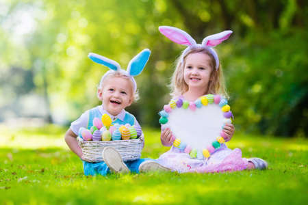 Foto für Little boy and girl having fun on Easter egg hunt. Kids in bunny ears and rabbit costume. Children with colorful eggs in a basket. Toddler kid and baby play outdoor. Blank board for your text. - Lizenzfreies Bild