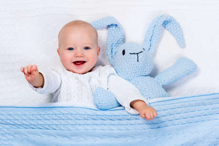 Foto de Funny little baby wearing a warm knitted jacket playing with toy bunny relaxing on white cable knit blanket in sunny nursery. Kids winter clothing and bedding. Hand made toys and textile for children. - Imagen libre de derechos