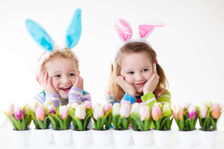 Photo pour Happy children celebrate Easter at home. Boy and girl wearing bunny ears enjoying egg hunt. Kids playing with color eggs and flower basket. Spring crafts and art for toddler child and preschooler kid. - image libre de droit