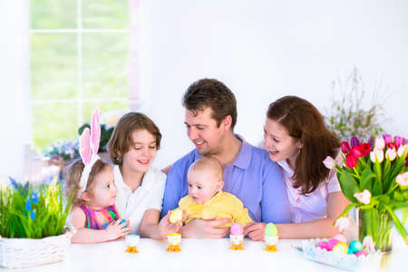 Photo pour Happy young family with three children - teenager boy, cute little toddler girl with bunny ears and a newborn baby - enjoying Easter breakfast in a white sunny dining room with a big garden window - image libre de droit