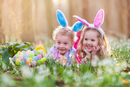 Foto für Kids on Easter egg hunt in blooming spring garden. Children with bunny ears searching for colorful eggs in snow drop flower meadow. Toddler boy and preschooler girl in rabbit costume play outdoors. - Lizenzfreies Bild