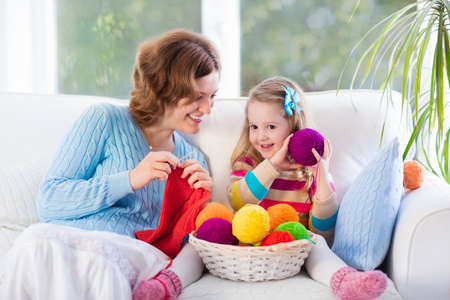 Mother and daughter knitting woolen scarf. Mom teaching child to knit. Crafts and hobby for parents and kids. Toddler girl kid with wool yarn in a basket. Knitted clothing for family with children.