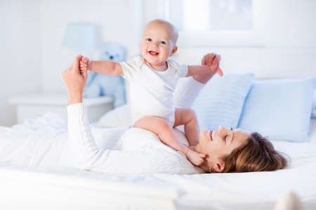 Foto de Mother and child on a white bed. Mom and baby boy in diaper playing in sunny bedroom. Parent and little kid relaxing at home. Family having fun together. Bedding and textile for infant nursery. - Imagen libre de derechos