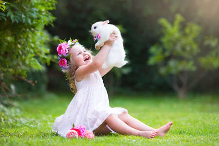 Foto de Girl playing with real rabbit in sunny garden. Child and bunny on Easter egg hunt in flower meadow. Toddler kid feeding pet animal. Kids and pets play.  Fun and friendship for animals and children. - Imagen libre de derechos