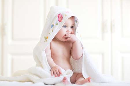 Photo pour Adorable baby girl sitting under a hooded towel after bath - image libre de droit