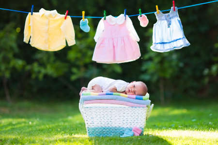 Photo pour Newborn baby on a pile of clean dry towels. New born child after bath in a towel. Family washing clothes. Kids wear hanging on a line outdoors in summer garden. Infant apparel, textile for children. - image libre de droit
