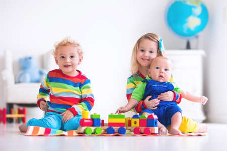 Foto de Children playing with wooden train. Toddler kid and baby play with blocks, trains and cars. Educational toys for preschool and kindergarten child. Boy and girl build toy railroad at home or daycare. - Imagen libre de derechos