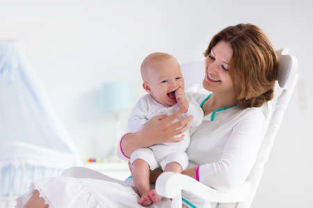 Photo for Young mother holding her newborn child. Mom nursing baby. Woman and new born boy in white bedroom with rocking chair and blue crib. Nursery interior. Mother playing with laughing kid. Family at home - Royalty Free Image