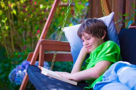 Photo pour Happy school boy reading a book in the backyard. Child relaxing in a garden swing with books. Kids read during summer vacation. Children studying. Teenager kid doing homework outdoors. - image libre de droit